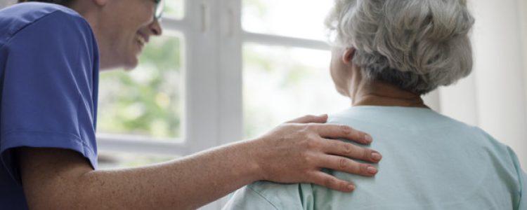 Eine Pflegerin legt behutsam ihre Hand auf die Schulter einer Bewohnerin